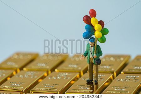 selective focus on miniature figure happy man holding balloons standing on shiny gold bullions as financial investment and safe haven concept.