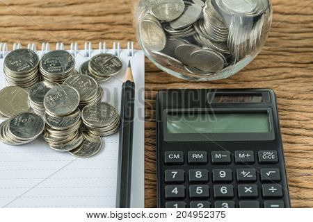selective focus on stack of coins with pencil and note book calculator as financial saving concept