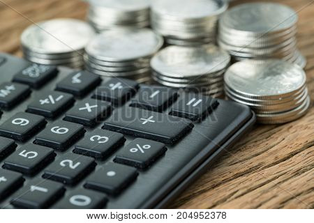 financial saving concept as selective focus on calculator with stack of coins in the background on wood table.