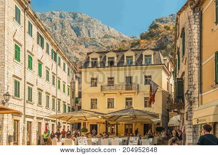 KOTOR, MONTENEGRO - AUGUST 24, 2017:  Picturesque cafe in the ancient city square. Kotor is listed as a World Cultural Heritage by UNESCO.