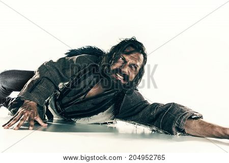 Actor in makeup, a poor man isolated on white studio background. The bum in canvas rags. concept of vagrancy and survival poster