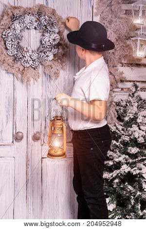 A 10 years boy knocking at door, while holding lantern in his hand at Christmas