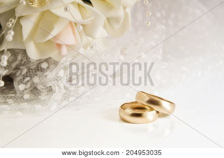 Wedding rings and bridal bouquet on a light background. Horizontal format. Indoors. Without people. Color. Photo.