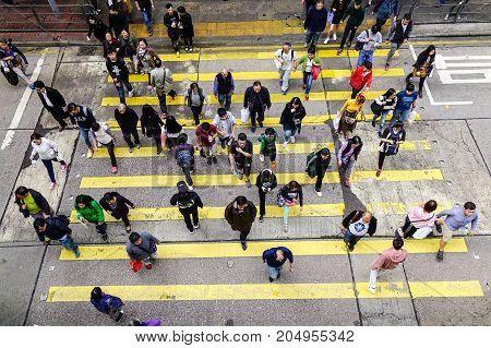People Walking Across Street In Hong Kong