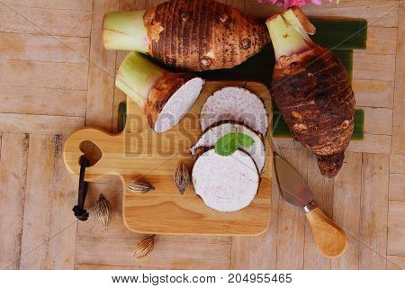 Fresh taro root for cooking on wood background