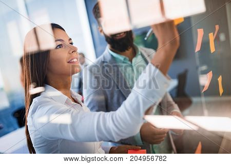 Picture of young designers sticking notes in office