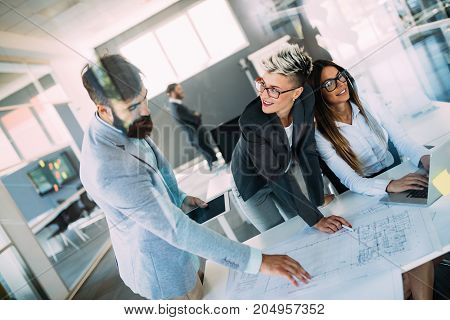 Portrait of young perspective architects discussing in office