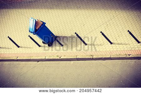 Cleanliness in city objects concept. Minimalist photo of blue trash can on street pavement