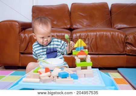 Cute Asian 20 months / 1 year old toddler baby boy child play with colorful wooden blocks. Kid playing with educational toys while eating snack in living room at home photo in real life interior