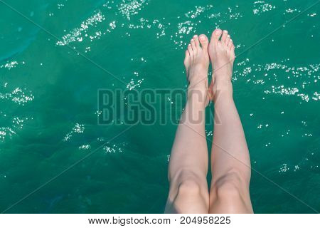 Young Female Legs Hanging Over The Sea Water