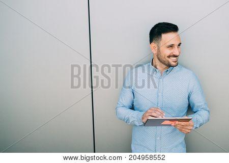 Portrait of handsome successful smiling businessman holding tablet