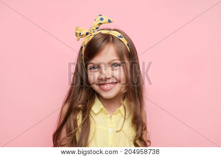 Little girl wearing headband and smiling at camera on pink background.