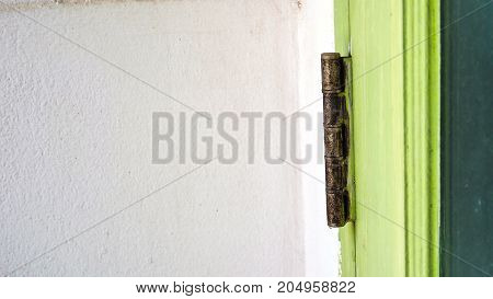Door Hinge Rusted background has copy space white wall door is soft green color Photo close up see the detail when the long times ten years ago.