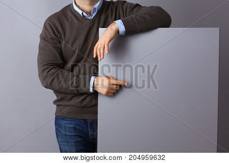 Young businessman standing near a blank board .