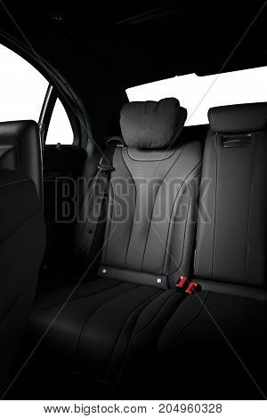Back passenger seats in modern luxury car, frontal view, black leather