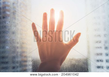 Depression,loneliness On City, Woman Hand Touch Window With A Rain Drops On City Background.sun Rays