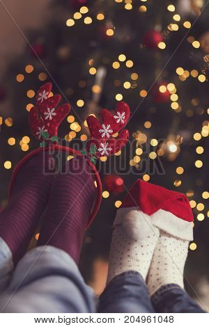 Detail of male and female feet wearing warm winter socks with small Santa's hat and antlers placed on the table with Christmas tree and Christmas lights in background. Selective focus on the antlers