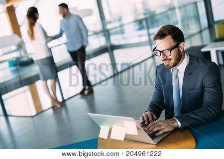 Young handsome male architect working on laptop in office