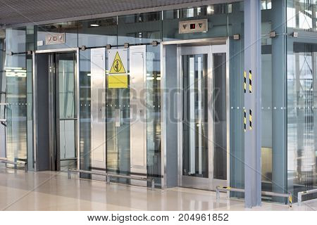 Modern elevator or lift doors made of metal and glass in building with lighting.Modern elevator in national airport