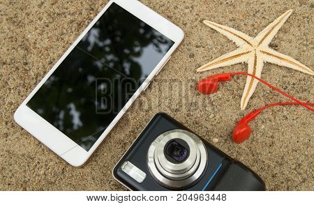 The concept of travel planning and vacation on the sea sand. Top view smartphone, camera, starfish, headphones.