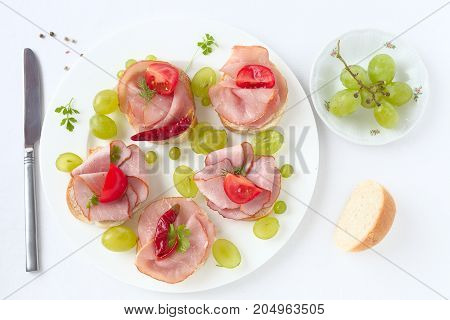 Ham sandwiches with tomato and grapes on a white plate.