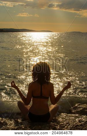 Young girl practicing yoga on the seaside during the sunset