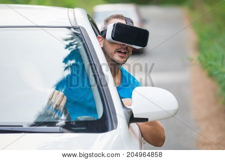 Portrait of young man using virtual reality glasses and looking through car window. Road in the background.