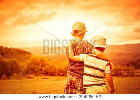 Child in travel trip against the backdrop of forest meadow mountains and sky. Rural scene. Two children boys together view from the back. Retro toned.