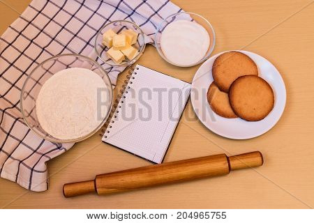 Flour sugar butter empty notebook prepared cookies and rolling pin