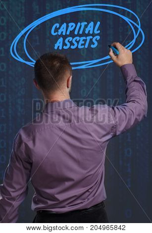 Business Technology Internet and network concept. Young businessman working on a virtual screen of the future and sees the inscription: Capital assets