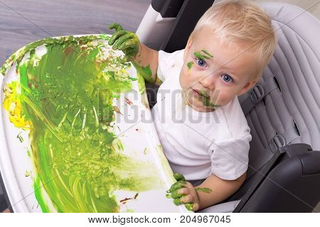 Portrait of a cute little boy messily playing with paints.