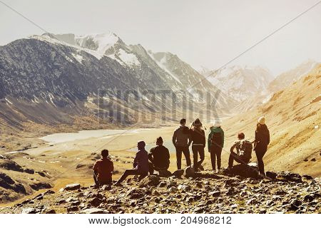 Group of friends or tourists stands at mountains viewpoint. Travel or tourism concept