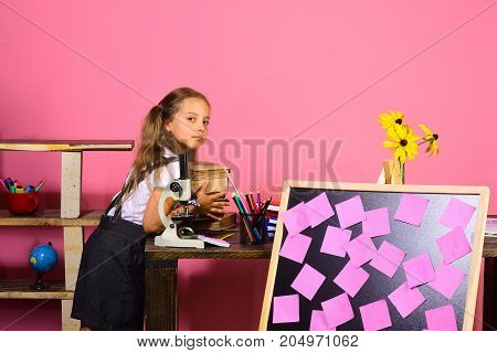 Girl Puts Books On Desk With Microscope And Blackboard
