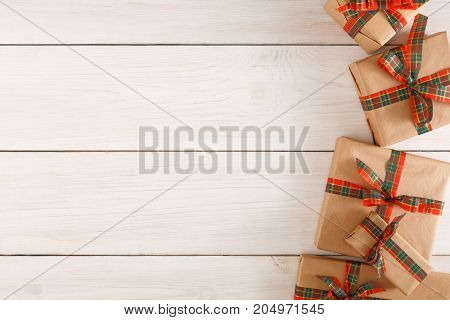 Gift boxes border, top view with copy space on white wooden table background. Frame of colored packages with red, green ribbons for christmas, valentine day or birthday