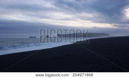 Sunset on Dýrholaey cape, view from Reynisfjara black sand beach on Iceland