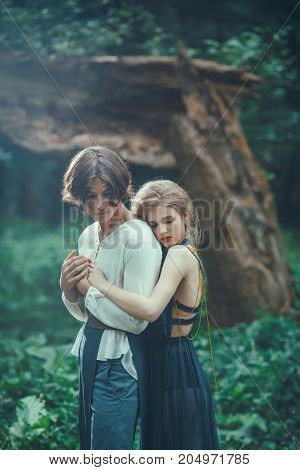 Young couple of elves in love in magical forest agaist the broken tree outdoor on nature. Fairy tale love, relationship and magik people concept. Woman ambracing man
