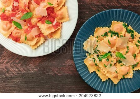 Overhead photo of two plates of ravioli, one with green sauce and the other with tomato sauce, with grated Parmesan cheese and basil leaves, shot from above on rustic background with place for text