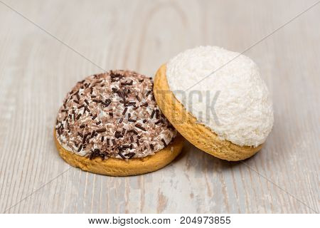 Two round delicious cookies on white wooden table