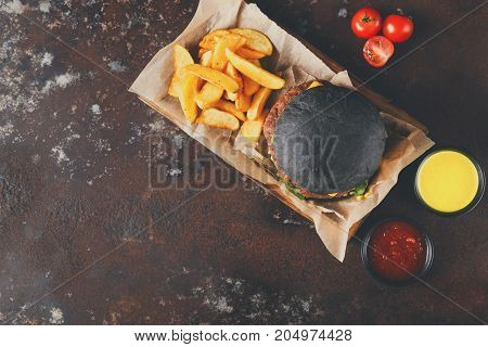 Black bun burger with potato wedges and sauces on wooden tray top view. Appetizing cheeseburger with cutlet and tomatoes, fast food concept