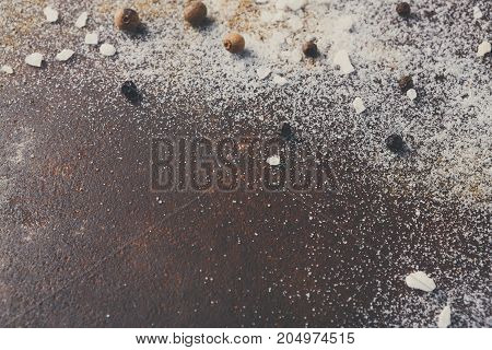 Scattered salt and pepper on dark background. Spices on kitchen table, creative cooking backdrop, copy space