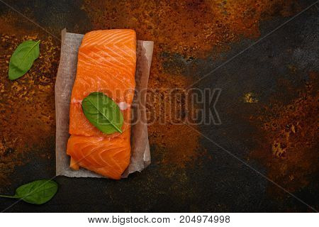 Raw fresh salmon steak with spinach lieaves over rust background. Space for text