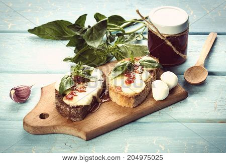 Bruschetta with mozzarella cheese tomato confiture and green basil leaf on blue background