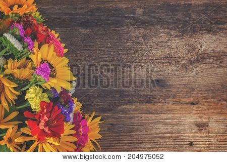 Bright bouquet with fresh fall flowers on wooden textured table with copy space, retro toned
