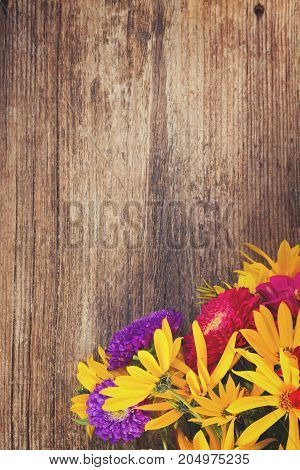 Bright fall bouquet on wooden background with copy space, retro toned