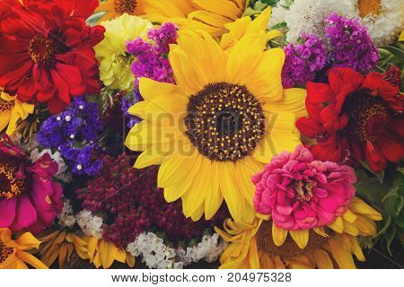 Bright bouquet with fresh fall flowers close up background, retro toned