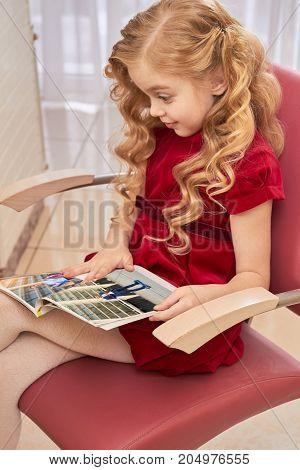 Amazed child reading fashion magazine. Surprised little girl. How media influences children.