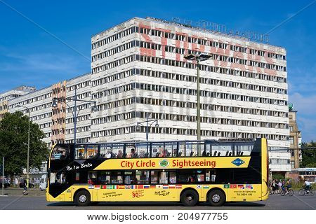 BERLIN, GERMANY - AUGUST 08, 2017: Tourists during a city tour through the streets of Berlin in a yellow bus