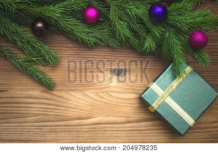Christmas present box in fir tree branches with toy balls around on burnt wooden board surface background with copy space. Christmas decorations.
