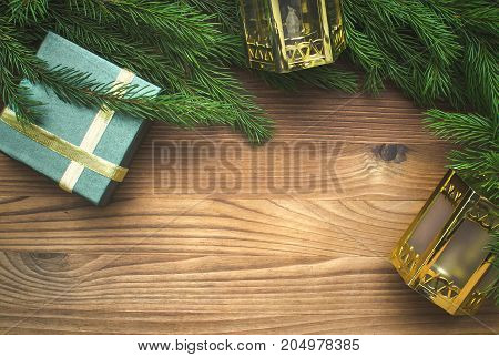 Christmas present box in fir tree branches with toy christmas lanterns around on burnt wooden board surface background with copy space. Christmas decorations.