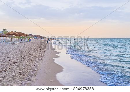 EL KANTAOUI TUNISIA - SEPTEMBER 3 2015: The sand beach of famous tourist resort is the perfect place to relax and enjoy the evening on September 3 in El Kantaoui.